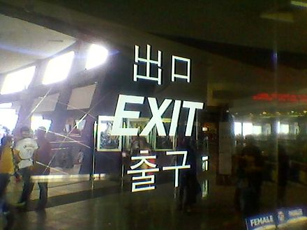 "Multilingual sign at an exit of SM Mall of Asia in Pasay City, Philippines. Three or four languages are shown: Japanese/Mandarin Chinese (""deguchi"" or ""chukou"", respectively), English (""exit"") and Korean (""chulgu""). While Filipinos themselves are anglophone, such signs cater to the growing number of Koreans and other foreigners in the country. SPM A7786.jpg"