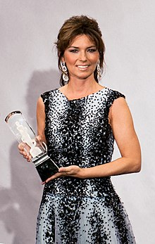 Shania Twain wearing a black and white dress and earrings holds an award statuette in both hands