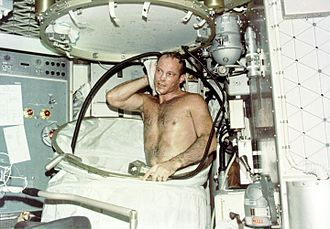 Hygiene - Astronaut taking a hot bath in the crew quarters of the Orbital Workshop (OWS) of the Skylab space station cluster in Earth orbit. In deploying the shower facility the shower curtain is pulled up from the floor and attached to the ceiling. The water comes through a push-button shower head attached to a flexible hose. Water is drawn off by a vacuum system.