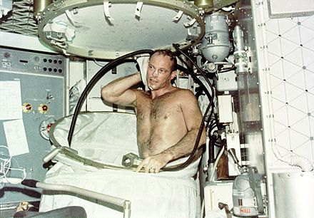 Astronaut taking a hot bath in the crew quarters of the Orbital Workshop (OWS) of the Skylab space station cluster in Earth orbit. In deploying the shower facility the shower curtain is pulled up from the floor and attached to the ceiling. The water comes through a push-button shower head attached to a flexible hose. Water is drawn off by a vacuum system. Showering on Skylab (9456594881).jpg