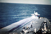 Looking forward at the bow of an aircraft carrier. A small jet fighter is in the process of being launched; it has just reached the end of the steam catapult. Flight deck personnel are standing clear.