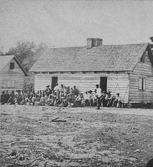 Plantation complexes in the Southern United States - 1862 photograph of the slave quarter at Smiths Plantation in Port Royal, South Carolina. The slave house shown is of the saddlebag type.