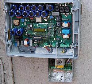 Power inverter - Internal view of a solar inverter. Note the many large capacitors (blue cylinders), used to store energy briefly and improve the output waveform.
