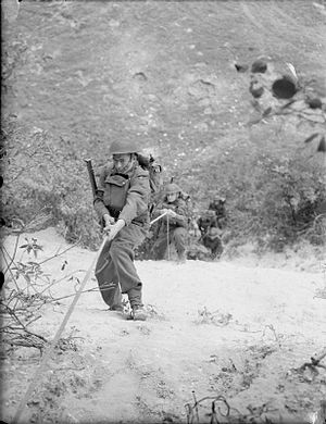 43rd (Wessex) Infantry Division - Soldiers of the 4th Battalion, Wiltshire Regiment climbing up the sheer face of a chalk quarry during 'toughening up' training at Leeds in Kent, England, 18 September 1941.