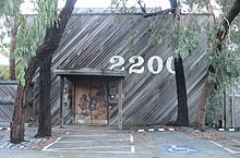 "Large, wooden building with a brown door (showing woodland animals play musical instruments) located in the bottom, centre left, and the large numbers ""2200"" painted in white above the door, centre-right. Asymmetrical trees with hanging foliage frame the building on all sides, while on the asphalt in the foreground, there are parking spaces and a disabled person sign."