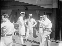 group shot of three men in naval uniform and one man in civilian dress talking to them