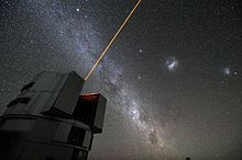Orange laser beam from a telescope into the night sky