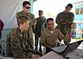 U.S. Marine Corps Capt. Amelia Griffith, left, a civil affairs officer with the Joint Civil Military Operations Task Force, reviews a presentation with Philippine Marine Corps Capt. Mike Mortel during a social 130318-N-VN372-006.jpg