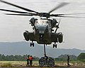 U.S. Marines from the 31st Marine Expeditionary Unit attach a pallet of construction supplies to a CH-53E Super Stallion helicopter.jpg