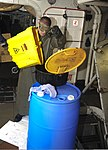 U.S. Navy Aviation Ordnanceman Airman Kevin Shumaker disposes of used hydraulic fluid aboard the aircraft carrier USS Dwight D. Eisenhower (CVN 69) Aug. 22, 2013, at Naval Station Norfolk, Va 130822-N-JQ675-024.jpg