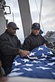 U.S. Navy Fire Controlman 2nd Class Cedric Bussey, left, and Quartermaster Seaman Recruit Tayler Simpkins fold a U.S. flag aboard the guided missile destroyer USS Stout (DDG 55) as the ship prepares to pull into 140119-N-UD469-288.jpg