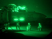 Mostly dark with green hue, this is a night-vision of jet aircraft and several mechanics kneeling close by. The aircraft's canopy is open.