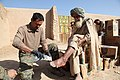 USN hospital corpsman checking afghan elder's foot for infection near Sangin Afghanistan.jpg
