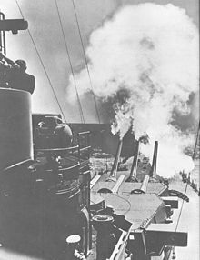 Six large guns in two turrets are aimed directly forward; the far trio are elevated extremely high and have a large amount of smoke emanating from them