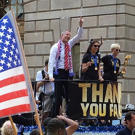 Lloyd celebrates the 2015 FIFA Women's World Cup win at the ticker tape parade in New York City, July 2015 USWNT victory parade Mayor De Blasio with Carli Lloyd and Megan Rapinoe.jpg