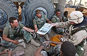US Navy 030404-M-0000D-001 Command Sgt. Maj. John Sparks, delivers copies of Stars and Stripes to U.S. Marines from Weapons Platoon, 3-2 India Company