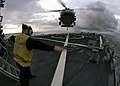 US Navy 050107-N-9079D-420 Boatswain's Mate 1st Class Shannon Mills, of San Francisco, Calif., signals an MH-60S Knighthawk helicopter onto the flight deck aboard the guided missile destroyer USS Benfold (DDG 65).jpg