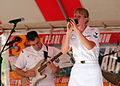 US Navy 050616-N-0000V-001 Musician 2nd Class Mallory McKendry sings to an audience as Musician 2nd Class Brain Nefferdorf plays the guitar during a public concert at the Pearl Harbor Navy Exchange mall.jpg