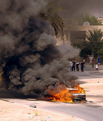 Human rights in post-invasion Iraq - An Iraqi vehicle burns in Baghdad after being hit by a mortar that was fired by insurgents, 8 August 2006