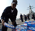 US Navy 080824-N-4044H-106 Boatswain's Mate Seaman Recruit Eddius Hucks stacks humanitarian aid supplies aboard the guided-missile destroyer USS McFaul (DDG 74), which will be put on pallets and distributed to the people of Geo.jpg