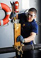US Navy 081022-N-2183K-131 Machinery Repairman 3rd Class Felipe Torres fills a ruptured pipe with oakum and wood.jpg