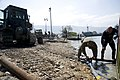 US Navy 100125-N-1134L-143 hief Warrant Officer 4 Jeff Barone works with a Marine to remove submerged container boxes.jpg