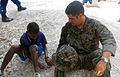 US Navy 100201-N-5808R-247 Hospital Corpsman 3rd Class Philip Davila plays marbles with a Haitian boy at the Heart to Heart orphanage.jpg