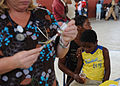 US Navy 100209-F-0261M-088 A volunteer nurse practitioner prepares an injection for a Haitian patient at an improvised clinic operated by the Crudem Foundation in a community gymnasium.jpg