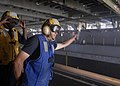 US Navy 100223-N-2000D-115 Seaman Jordan Luesebrink of South Sioux City, Neb., as he signals to the pilot of an air-cushioned landing craft (LCAC) during amphibious operations in the well deck of the amphibious dock landing shi.jpg