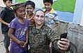 US Navy 111215-N-PB383-180 Sgt. Marcos Bustos poses for a photo with children during a community relation's event at the Help the Cambodian Childre.jpg
