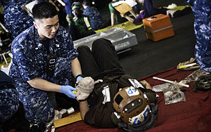 US Navy 120209-N-GC412-470 Hospital Corpsman 2nd Class Henry Nguyen treats a Sailor for simulated injuries during a mass casualty drill in the hang.jpg