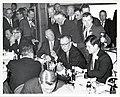 Unites States Senator Leverett Saltonstall speaks with Mayor John F. Collins in a crowded room with Member of the Massachusetts House of Representatives William Bulger (12306409613).jpg
