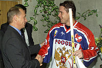 "An ice hockey player in his early thirties shakes hands with a middle-aged man dressed in a dark suit. The hockey player wears a white, red and blue jersey labeled ""РОССИЯ"" and holds a hockey stick."