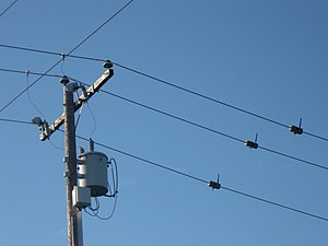 Wireless powerline sensor - Three powerline sensors hanging on conductors 2 meters to the right of a power pole with a distribution transformer and communication network node