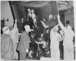 Photographie en noir et blanc montrant des ouvriers qui transportent une toile de grandes dimensions.
