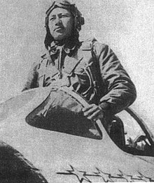 A Chinese man in a flight suit standing in the cockpit of an aircraft.