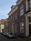 Pand met bakstenen lijstgevel met grote ramen en gepleisterde omlijste voordeur