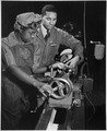 """Under the direction of Cecil M. Coles, NYA foreman, Miss Juanita E. Gray learns to operate a lathe machine at the... - NARA - 535809.tif"