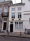 foto van Huis met eenvoudige witgeschilderde lijstgevel met schuiframen
