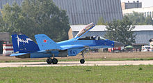 Side view of blue jet aircraft taxiing right with canopy open