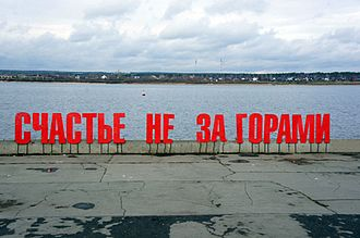 """Happiness is coming soon"" in red letters on a riverbank"