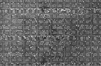 Electron microprobe - A section of the 1886VE10 microcontroller die as seen by an electron microprobe. The small bright cylinders are tungsten vias left over from a metalization etching process. The X-ray spectroscopy technique can be used to determine the material composition of the vias.