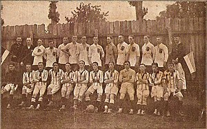 row of 11 men in striped kit sitting in front of another row of 11 men standing and dressed in plain kit, flanked by 4 other men