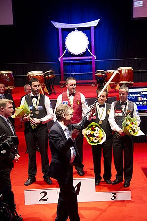 UMB World Three-cushion Championship - 2013 Award ceremony. Ludo Dielis hands over the diamant-cue to the winner Frederic Caudron. From Left to right: Vice world champion Filippos Kasidokostas, Caudron, Bronze medal winners Alexander Salazar and Dick Jaspers.