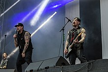 Joel Madden in the center signing into a microphone, and Benji Madden on the right playing guitar