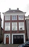foto van Pand met twee verdiepingen, versierde kozijnen en gesneden hoekconsoles onder schilddak met hoekschoorstenen