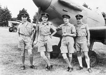 Four men wearing military uniforms posing in front of a propeller-driven aircraft