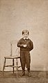 A young boy smiling and standing next to a wooden chair. Pho Wellcome V0030008ER.jpg