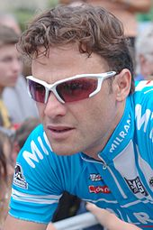 A man in his early thirties, wearing white-framed sunglasses with red lenses and a blue cycling jersey with white trim.