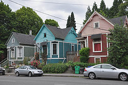 Photograph of three detached houses in a row along a street